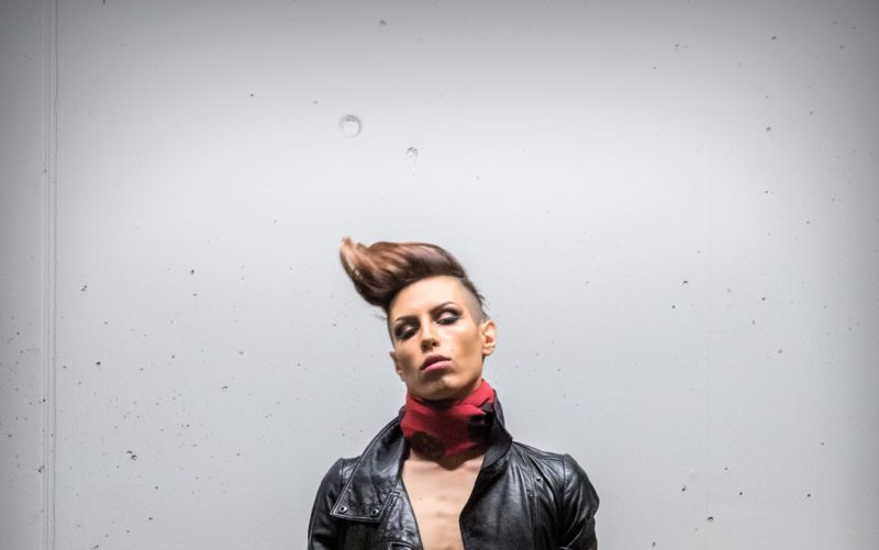 Person with punk hairstyle standing in front of a wall