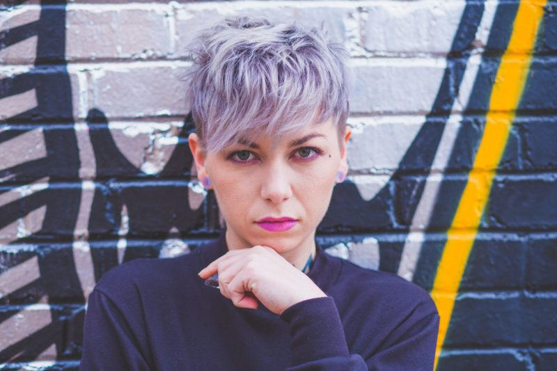 Person with pastel purple pixie hair standing in front of a graffited wall