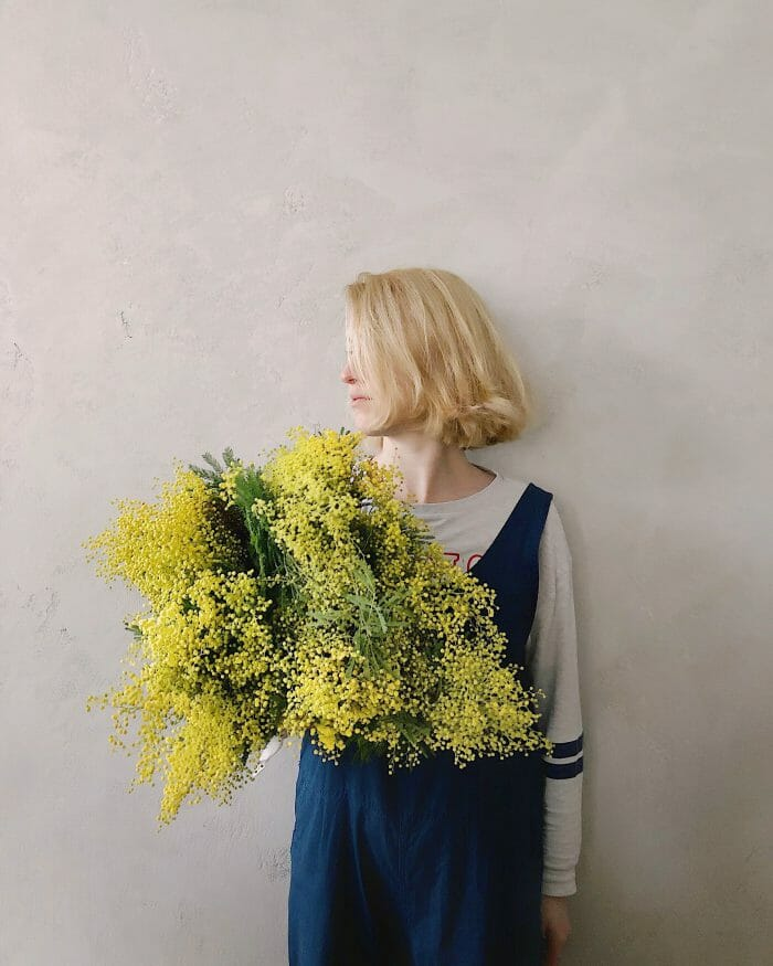 feminine blonde person holding a bouquet of flowers