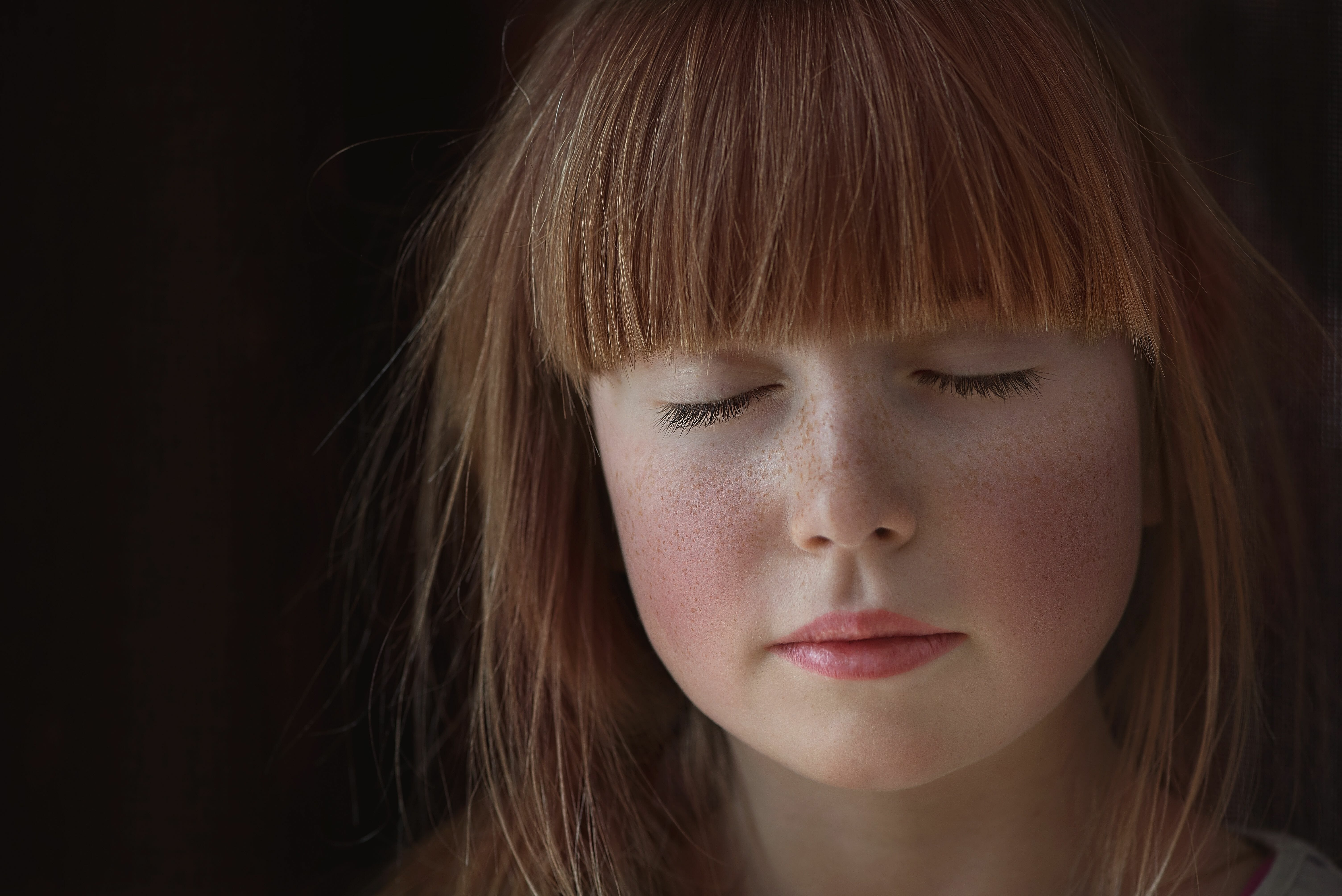 child with red hair and bangs