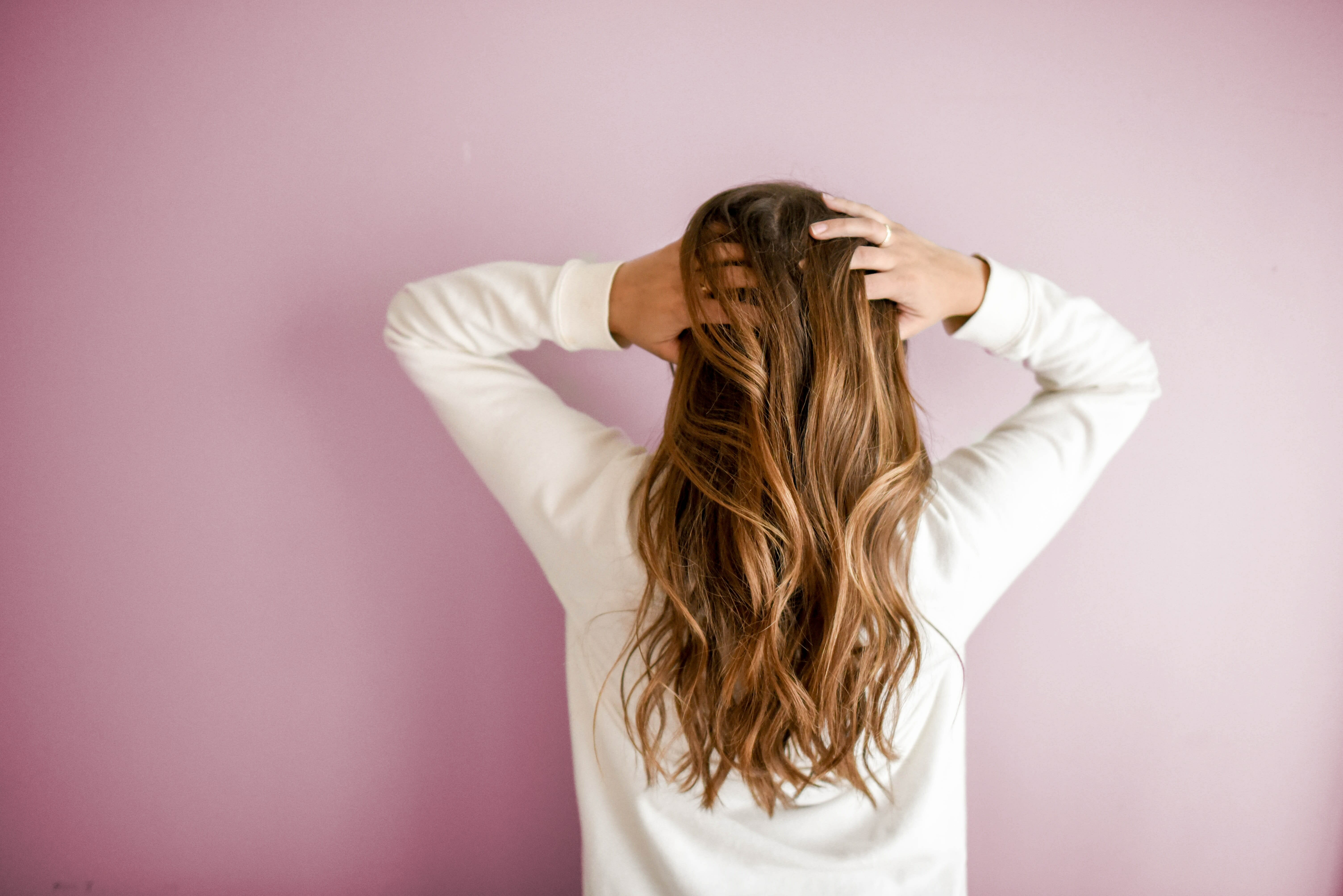 woman with long hair facing the wall and touching her head
