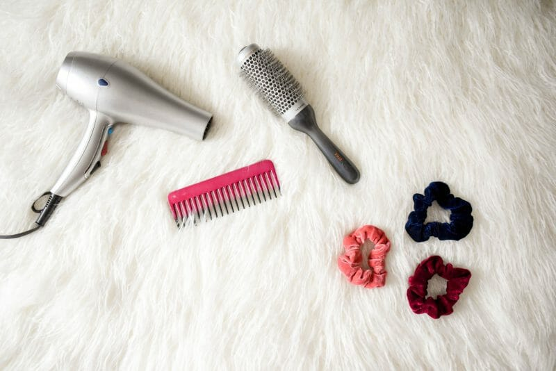 blow dryer, comb and brush accessories in fluffy background
