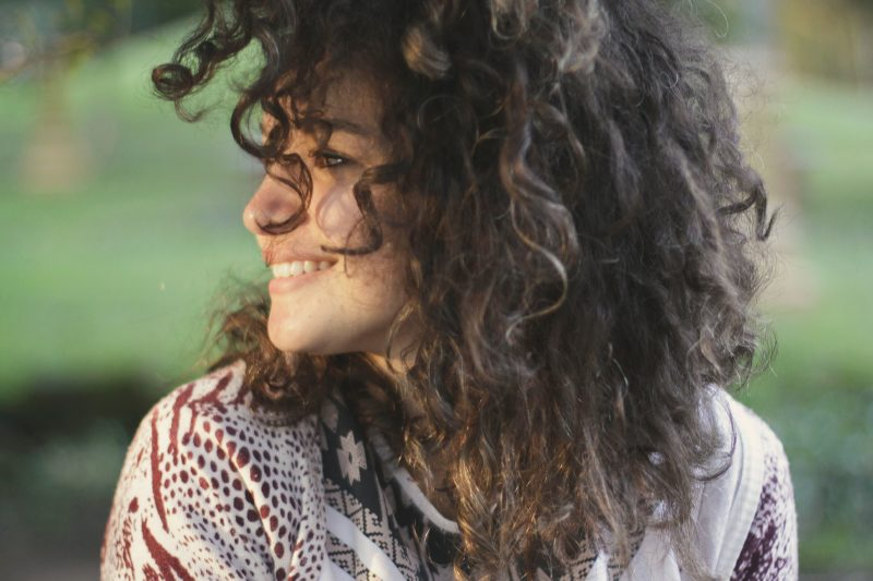 Woman with curly hair looking at her right