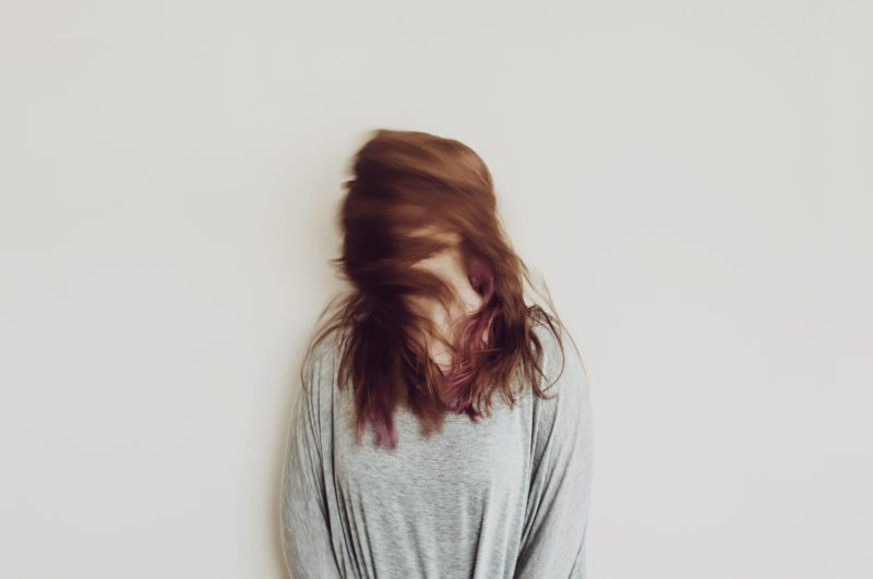 Person with long read hair in a gray sweater and background eith the face hidden